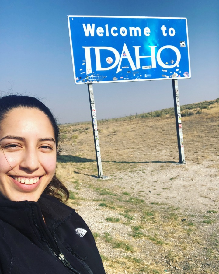 "Sarahi standing in front of the ""Welcome to Idaho"" sign"